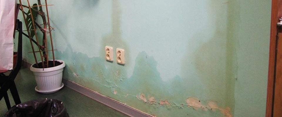 dłoń pokazująca palcem nazniszczoną ścianę